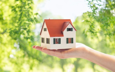 real estate, accommodation and eco friendly concept - close up of hand holding house or home model over green natural background