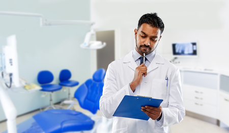 medicine, dentistry and profession concept - indian male dentist in white coat with clipboard over dental clinic office background
