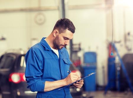 concept de service automobile, de réparation, d'entretien et de personnes - mécanicien automobile ou forgeron avec presse-papiers écrit à l'atelier Banque d'images