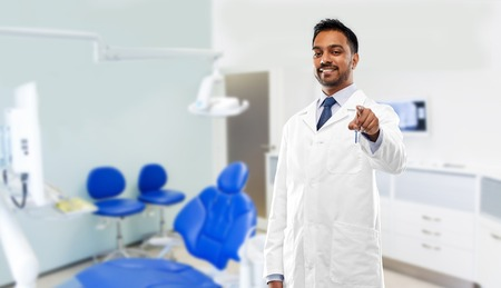 medicine, dentistry and healthcare concept - smiling indian male dentist in white coat pointing to you over dental clinic office background