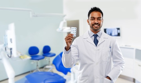 medicine, dentistry and healthcare concept - smiling indian male dentist in white coat with pills over dental clinic office background