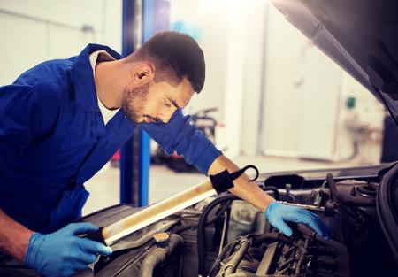 Autoservice, Reparatur, Wartung und Personenkonzept - Automechaniker mit Lampe, die in der Werkstatt arbeitet