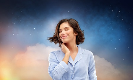 people and bedtime concept - happy young woman in pajama whipping her hair over starry night sky and cloud background
