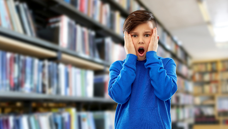 childhood, expressions and people concept - shocked or terrified boy touching his face over book shelves at library background