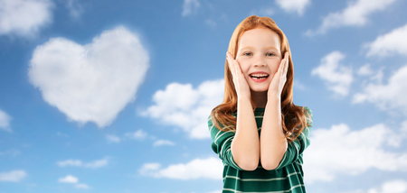 childhood, emotions and valentine's day concept - amazed red haired girl in green striped shirt over blue sky and heart shaped cloud clouds background Foto de archivo - 122616515