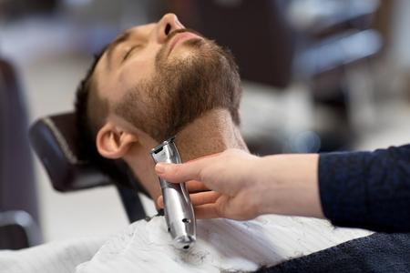 Pflege- und Personenkonzept - Mann und Friseur mit Trimmer oder Rasierer, der Bart im Friseursalon schneidet