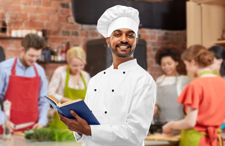 Male Indian chef reading cookbook at cooking class