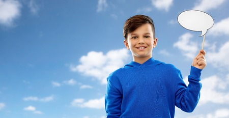 party props, photo booth and communication concept - smiling boy in blue hoodie holding blank speech bubble over blue sky and clouds background