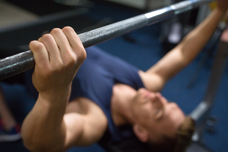sport, bodybuilding, lifestyle and people concept - close up of man or bodybuilder with barbell exercising in gym Stock fotó