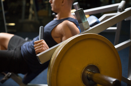 sport, fitness and people concept - close up of man exercising on gym machine Stock fotó