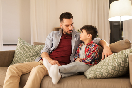 family, relationships and trust concept - father talking to his sad little son at home in evening