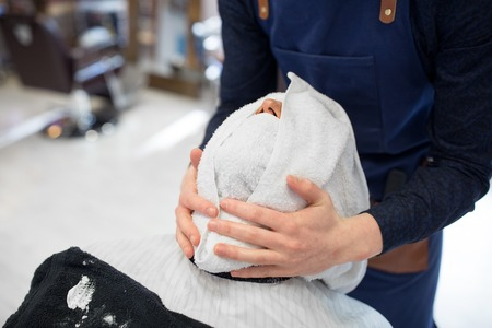 grooming, shaving and people concept - barber softening male clients face skin with hot towel at barbershop Фото со стока