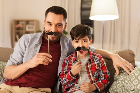 family, childhood and fatherhood concept - happy father and little son with mustaches party props having fun at home