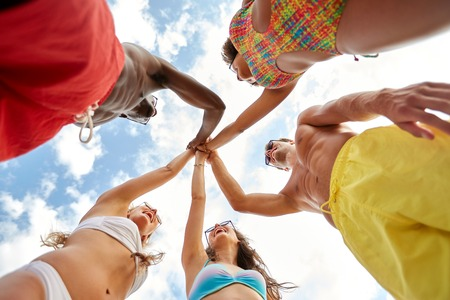 friendship, summer holidays and people concept - group of happy friends making high five over sky on beach