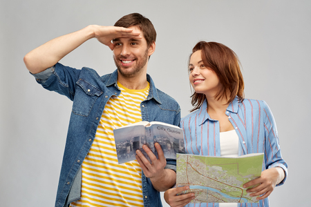 travel, tourism and vacation concept - happy couple of tourists with city guide and map over grey background