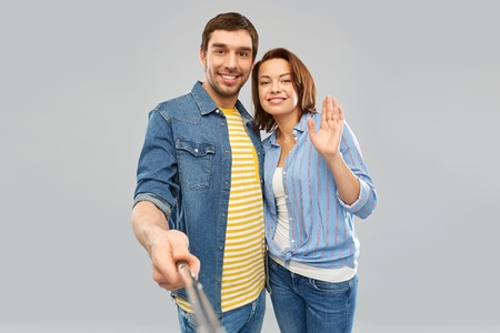 people concept - happy couple waving hand and taking picture by selfie stick over grey background