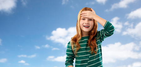 childhood, stress and people concept - happy smiling red haired girl in green striped shirt holding to her head over blue sky and clouds background 版權商用圖片