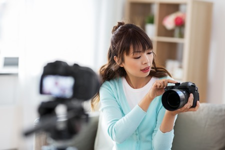 blogging, videoblog and technology concept - asian woman or blogger with photo camera recording video blog at home Banco de Imagens