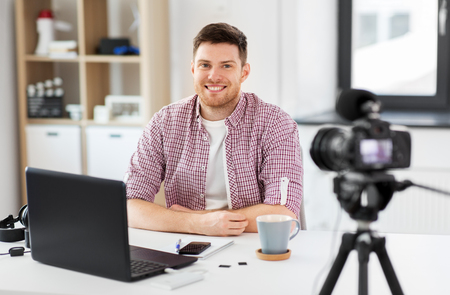 blogging, videoblog and people concept - male blogger with camera recording video at home office
