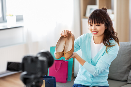 Blogging, technology, videoblog and people concept - happy smiling Asian woman or fashion blogger with flat shoes, shopping bags and camera recording video blog at home