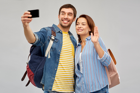 travel, tourism and vacation concept - happy couple of tourists with backpacks taking selfie by smartphone over grey background