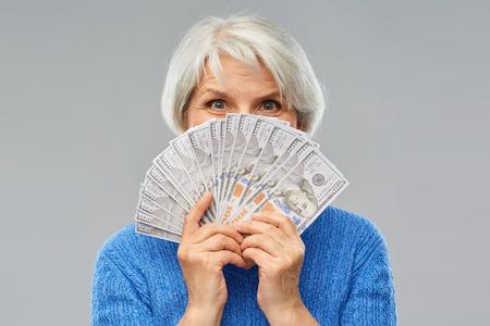 koncepcja oszczędności, finansów i ludzi - uśmiechnięta starsza kobieta chowająca twarz za setkami banknotów dolarowych