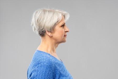 oude mensen concept - portret van senior vrouw in blauwe trui over grijze achtergrond Stockfoto