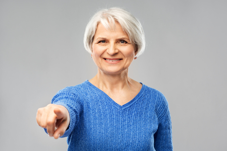 gesture, choice and old people concept - portrait of smiling senior woman in blue sweater pointing finger to you over grey background Stock Photo