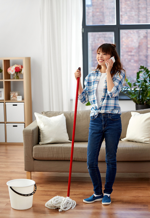 Asian woman with smartphone mopping floor at home