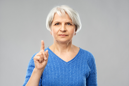 Serious senior woman pointing finger up