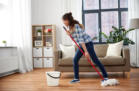 Gelukkige Aziatische vrouw met dweil die de vloer thuis schoonmaakt Stockfoto
