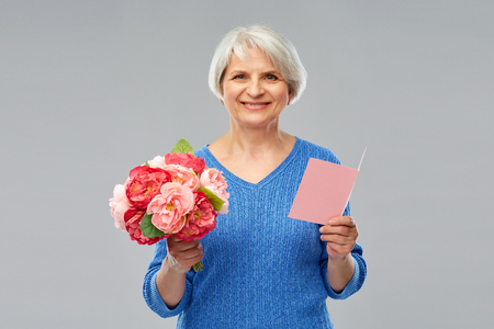 Happy senior woman with flowers and greeting card