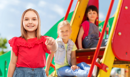 Smiling girl pointing to you on playground