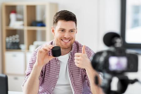 Male blogger with smart speaker videoblogging Banco de Imagens
