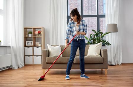 Azjatycka kobieta z miotłą zamiata podłogę i sprząta