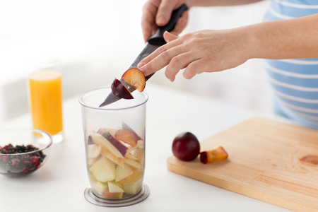 Pregnant woman chopping plums at home kitchen Stockfoto