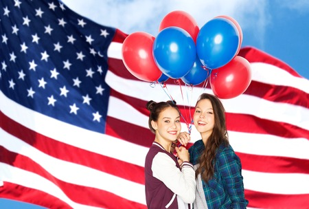 Teenage girls with balloons over american flag
