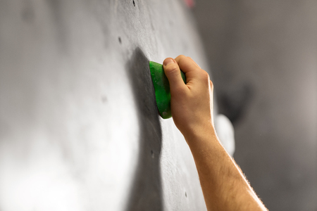 Male hand holding to indoor climbing wall