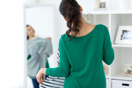 Close up of woman choosing clothes at home mirror