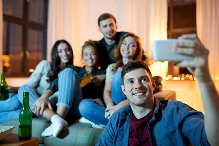 Happy friends taking selfie by smartphone at home Banque d'images - 122822951