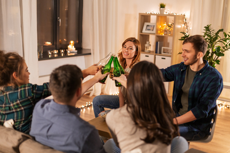 Friends clinking drinks at home in evening