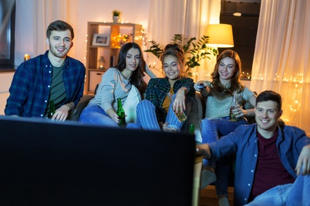 Happy friends with drinks watching tv at home Banque d'images - 122822969