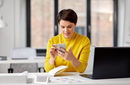 Smiling UI designer using smartphone at office
