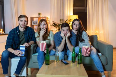 Friends with beer and popcorn watching tv at home Banque d'images - 122823034
