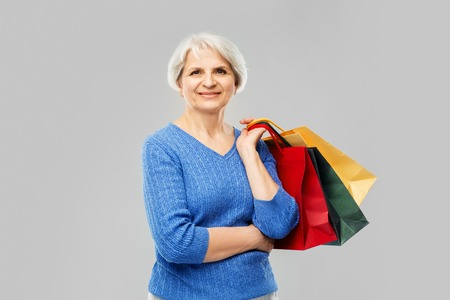 Senior woman with shopping bags over grey background