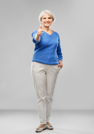 Smiling senior woman r showing thumbs up