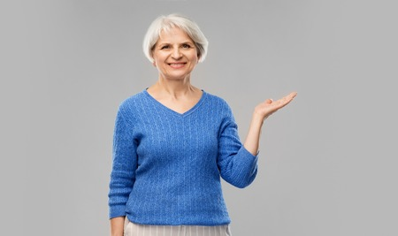 Senior woman holding something on empty hand Stockfoto