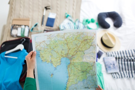 Woman with map at home preparing for travel Imagens