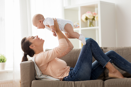 Happy mother playing with little baby boy at home Imagens