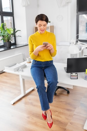 Happy woman with smartphone sitting on office desk Banque d'images - 122823048